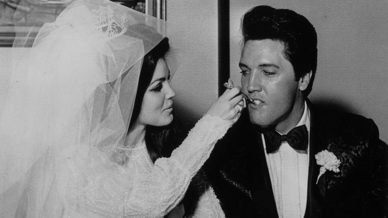 Elvis Presley and Priscilla Ann Beaulieu eating their wedding cake