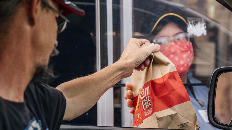 Drive-thru employee handing bag to driver