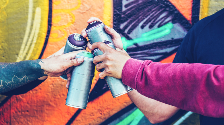 Hands with spray paint cans