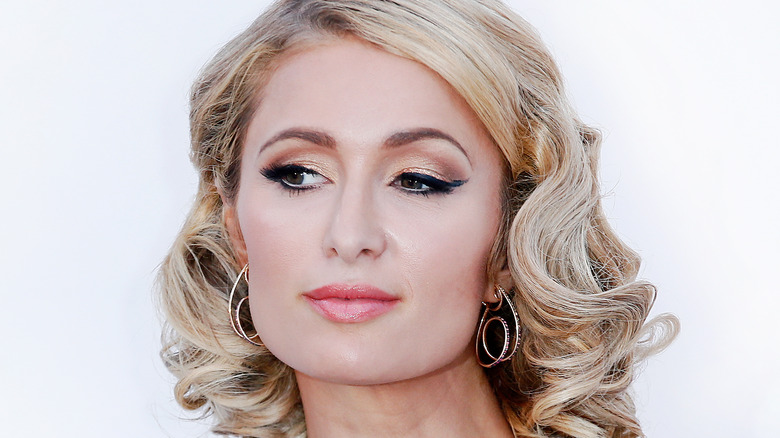 Closeup of Paris Hilton with curled hair and earrings