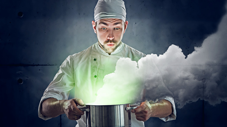 Cook looking into a pot with a mysterious recipe in it