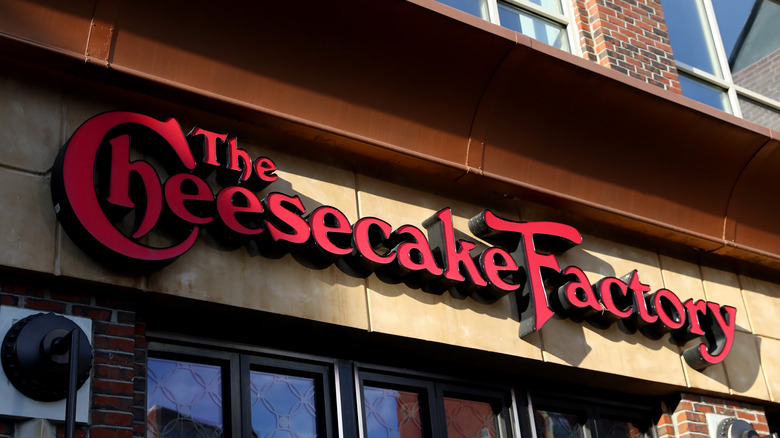 Red Cheesecake Factory logo on exterior of brown building