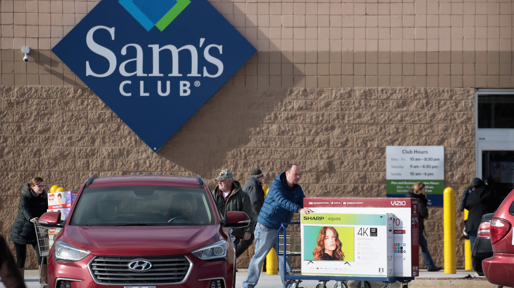 Man pushing cart with two television boxes outside of Sam's club. Maroon Hyundai parked nearby.