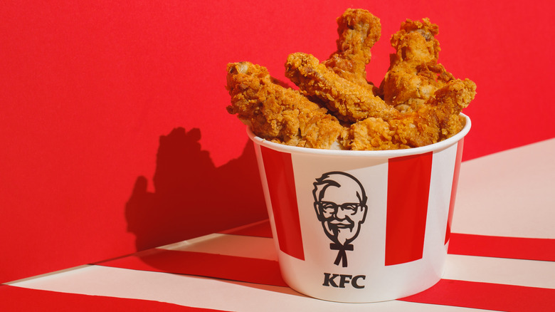 Bucket of Kentucky Fried Chicken against red wall