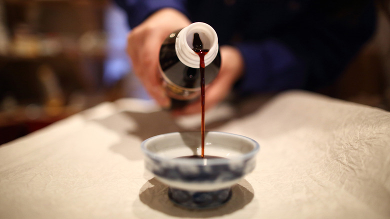 Pouring soy sauce into a dish