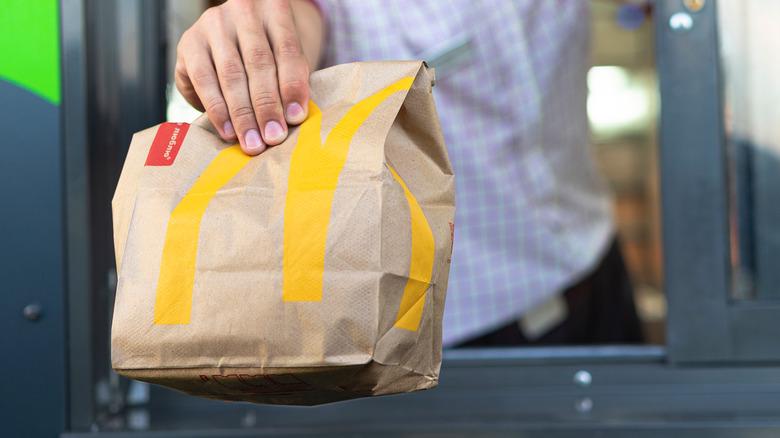 Drive-thru worker handing McDonald's bag to car