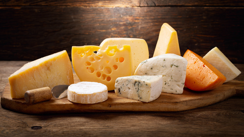 Assorted cheese on wooden cheeseboard