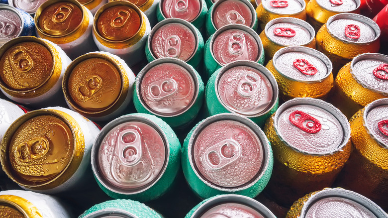 Rows of drink cans with condensation drops on them