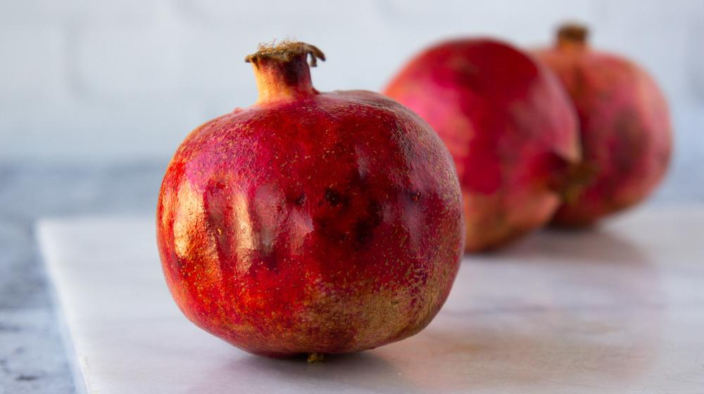 a pomegranate on white granite