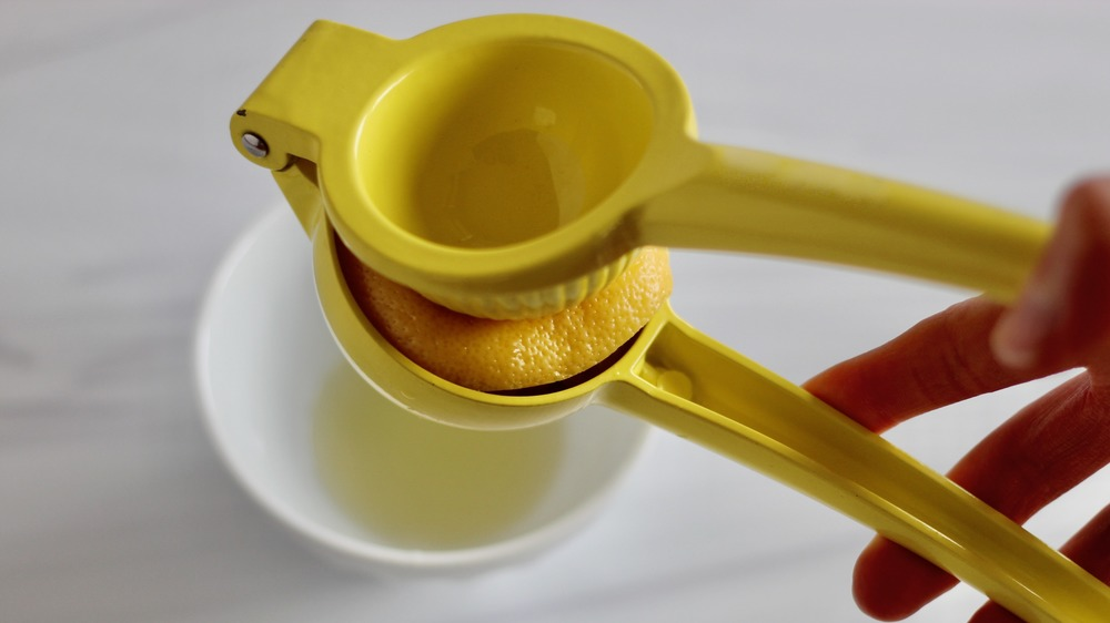 Squeezing lemon with yellow juicer