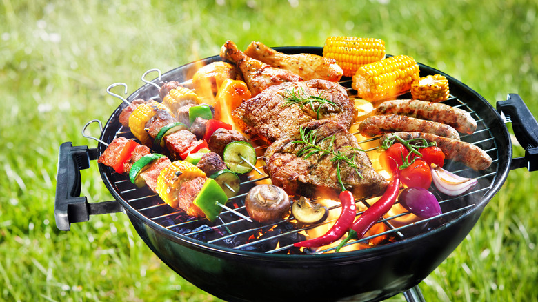 Meat and veggies on outdoor grill with grass in background
