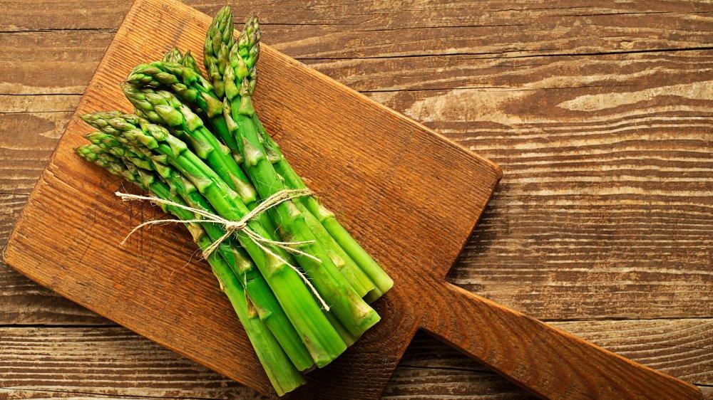 bundle of asparagus on cutting board