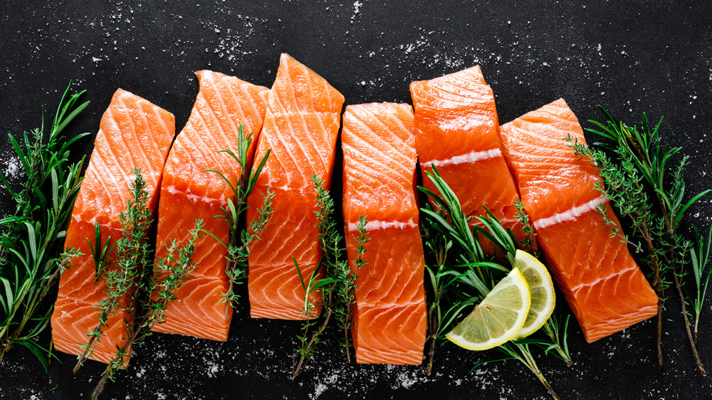 Pieces of raw salmon with salt and herbs