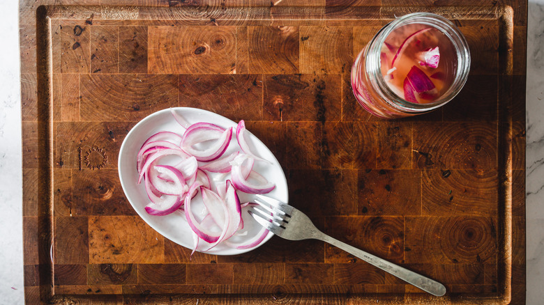 pickled onions on plate with jar