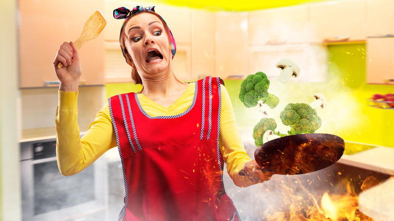 Woman catching pan of vegetables on fire