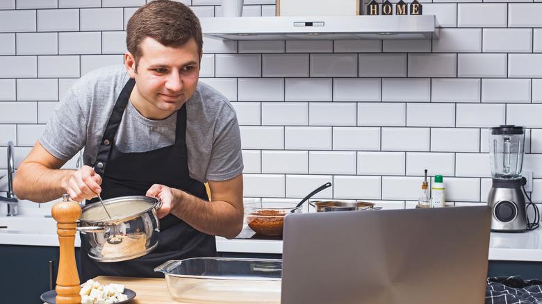 Man cooking recipe on laptop