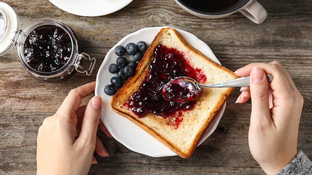 Woman spreading jam on toast