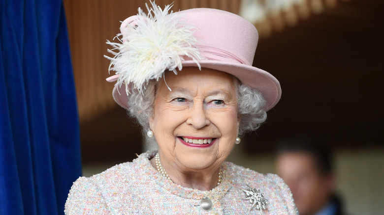 Queen Elizabeth smiling wearing pink sweater and pink hat