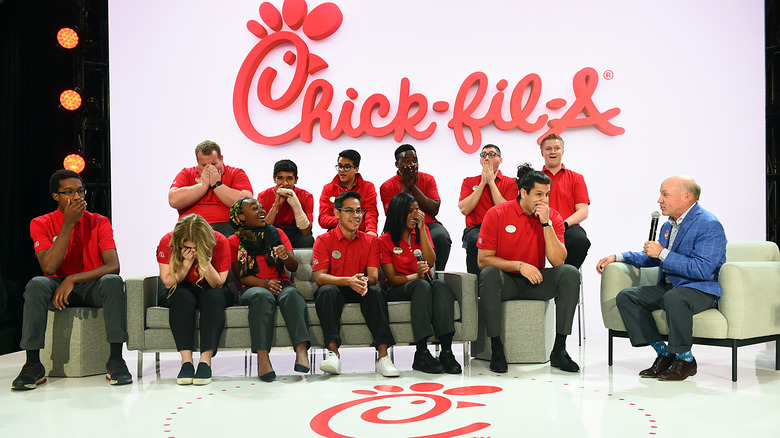 Chick-fil-A CEO Dan T. Cathy sitting on a stage with employees