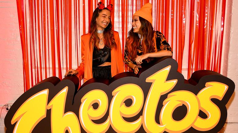 People wearing orange by Cheetos sign