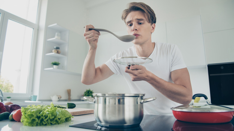 Person tasting pot of soup