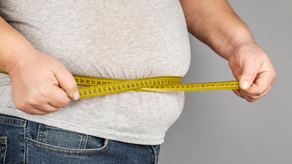 Man measuring large belly