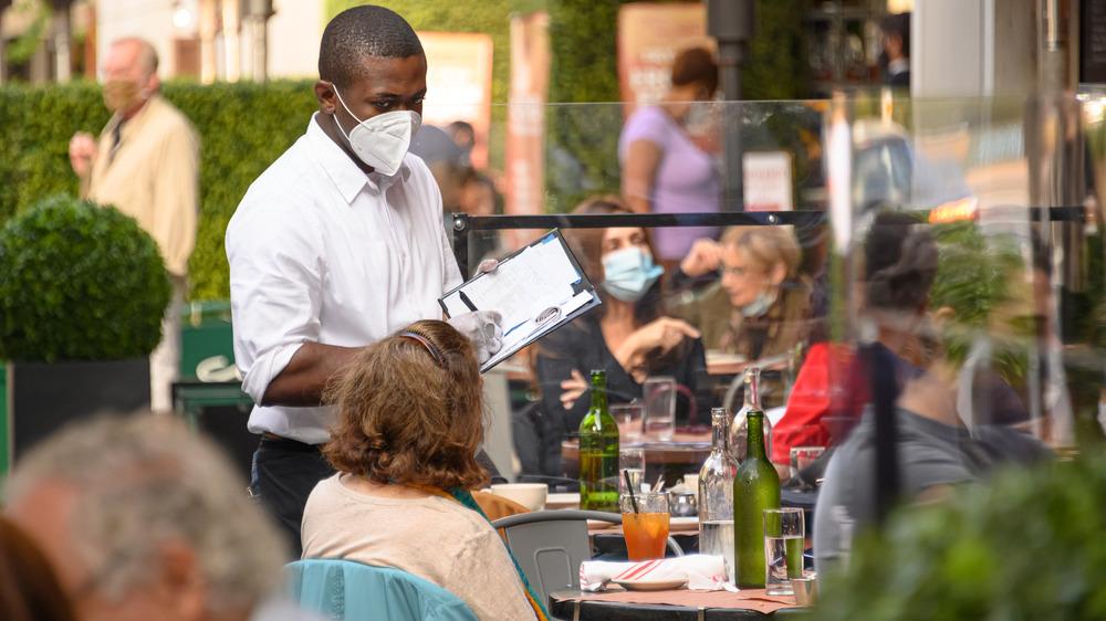Waiter wearing a mask