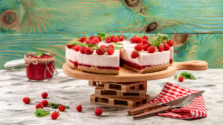 raspberry cheesecake sitting on a table with a fork and knife
