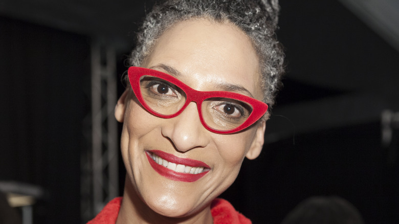 Carla Hall smiles with red glasses and red lipstick