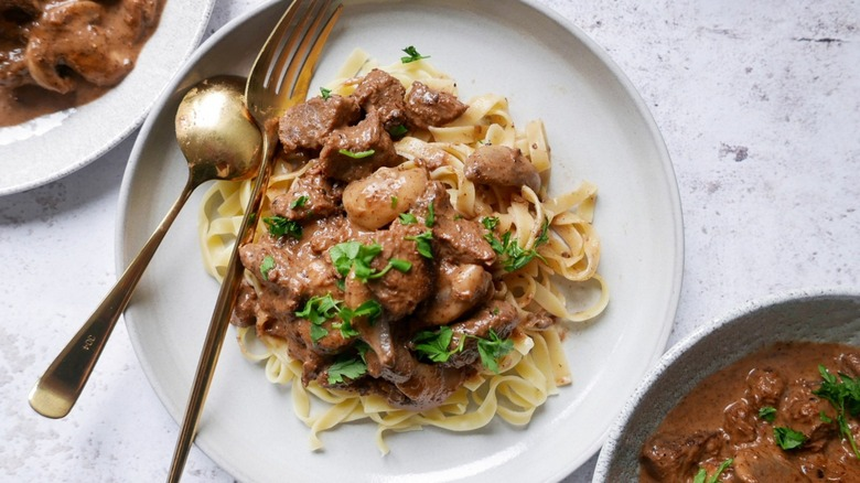Three plates filled with beef stroganoff.