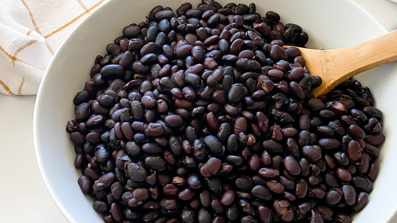 wooden spoon in bowl of black beans