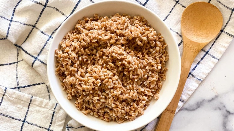 Cooked farro in a bowl with a wooden spoon