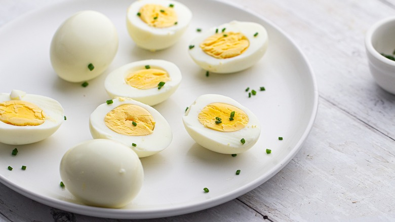 Hard-boiled eggs, cut and whole, on plate with chives