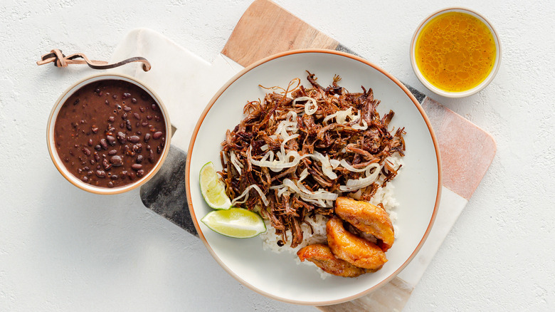 plate of instant pot vaca frita with bowl of beans