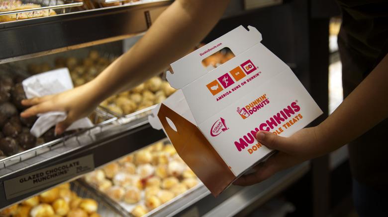 Dunkin' employee filling munchkin box