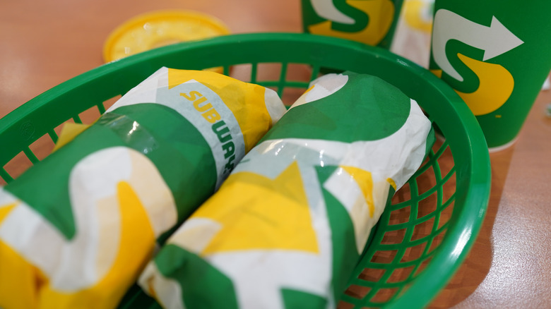 Green basket with wrapped Subway sandwiches