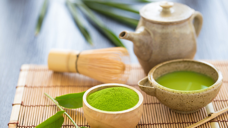 Two bowls of matcha with bamboo whisk and teapot