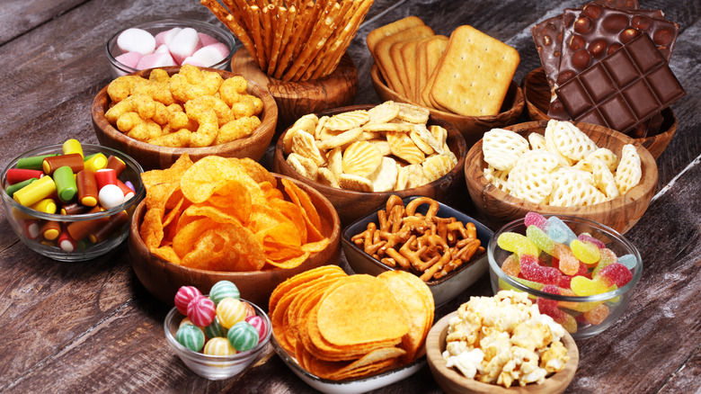 Unhealthy snacks in bowls on wooden table