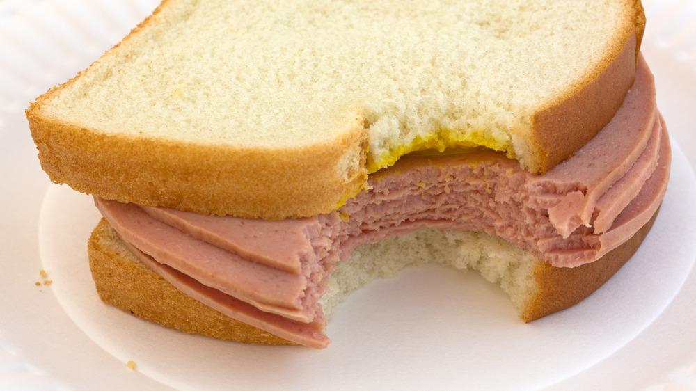 Bitten bologna sandwich with mustard