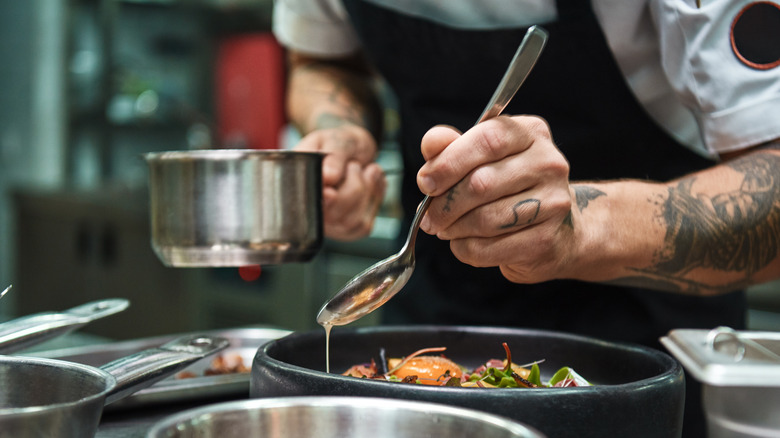 Chef pouring sauce with spoon