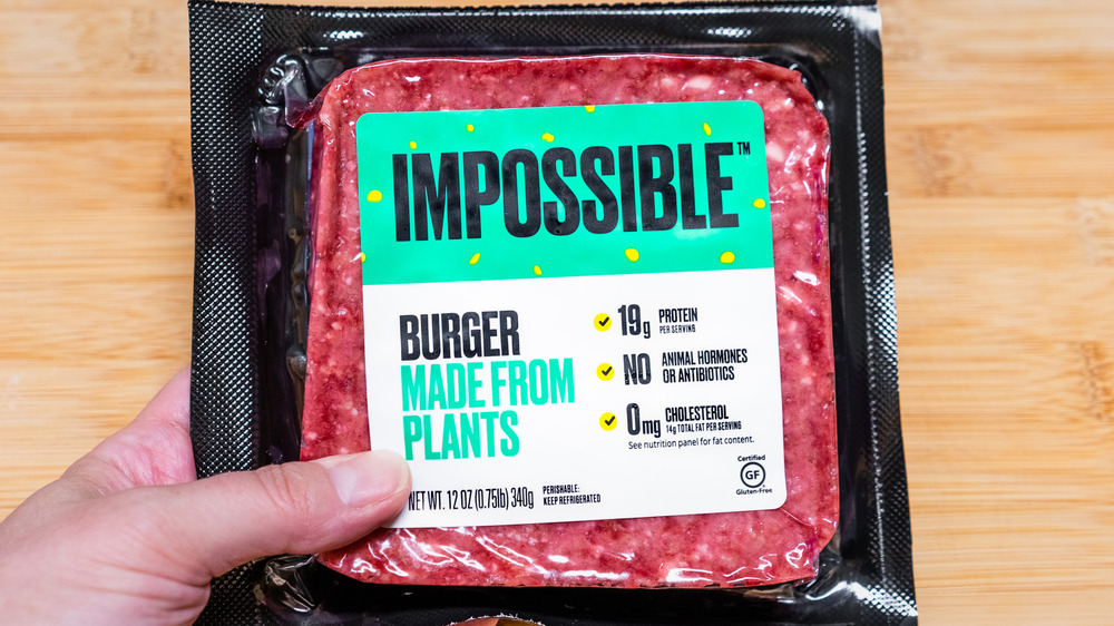Hand holding a package of Impossible burger meat