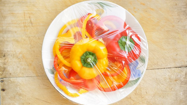 Bell peppers on plate with plastic wrap