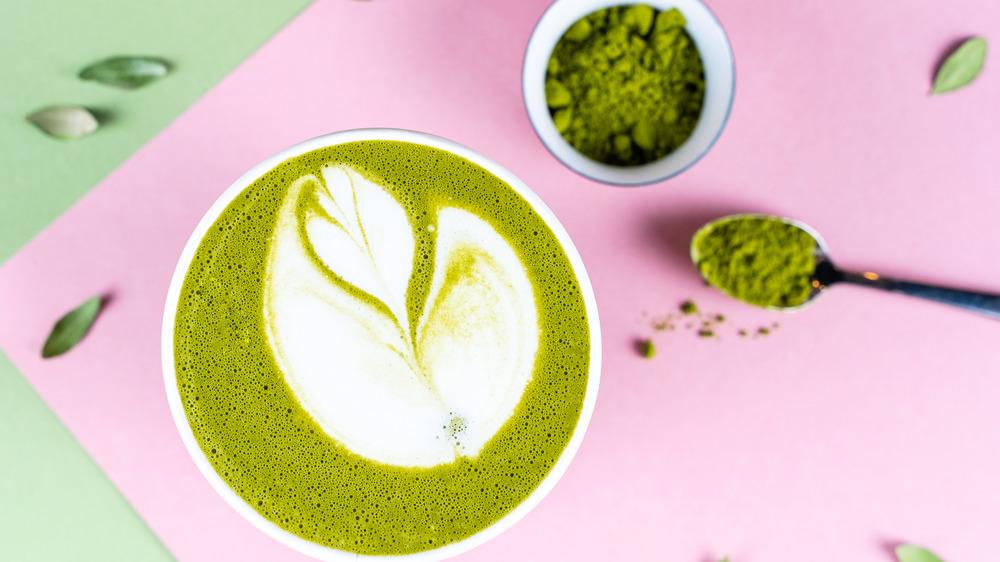 Matcha powder next to a matcha latte