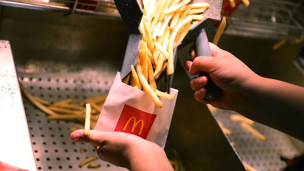 McDonald's employee filling a bag with French fries