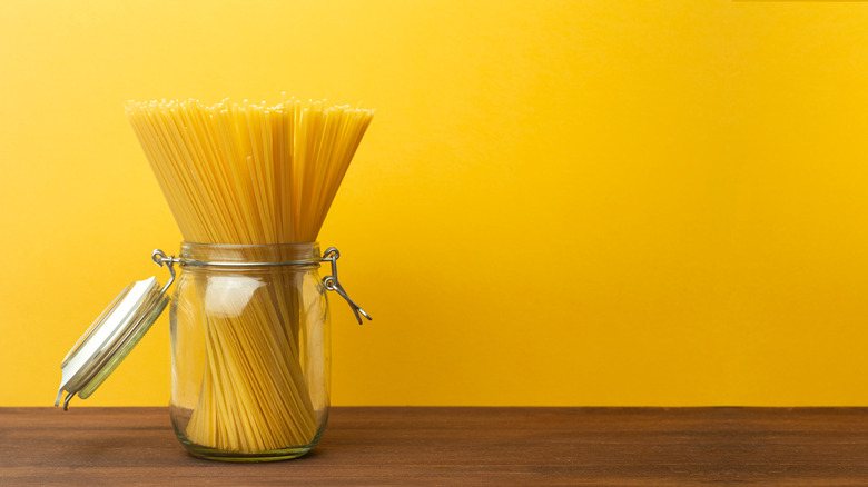 Jar of uncooked spaghetti against yellow backdrop