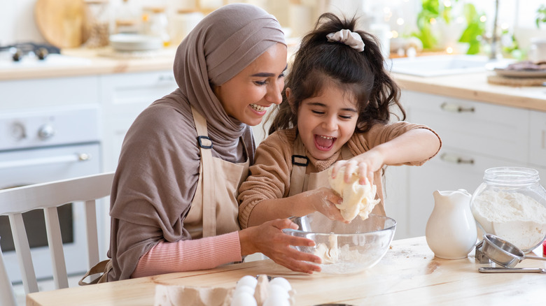 mom and daughter mixing dough