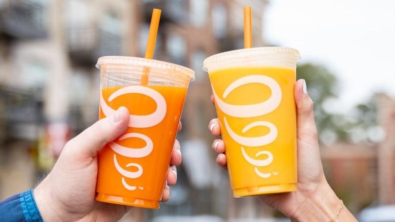 Two people holding orange Jamba smoothies