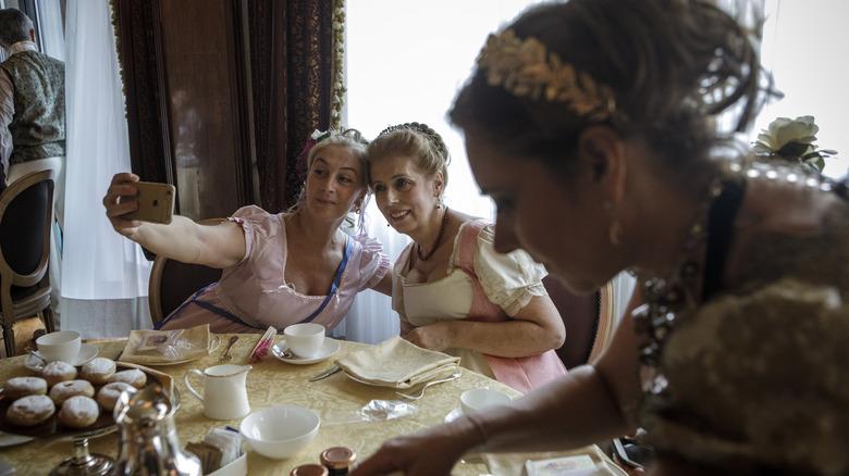 Women dining in vintage attire taking selfie