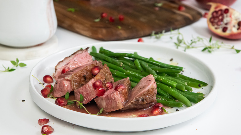 duck dish with pomegranate sauce and vegetables