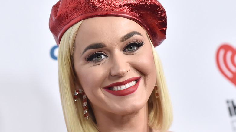Katy Perry blond with earrings and a red hat